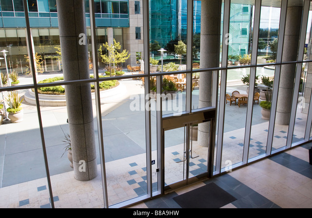 Attractive courtyard patio area as seen through the glass entrance to a modern office building complex - Stock Image