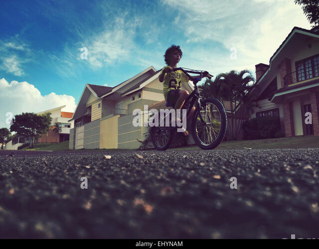 Low angle view of a boy riding a bicycle - Stock Image