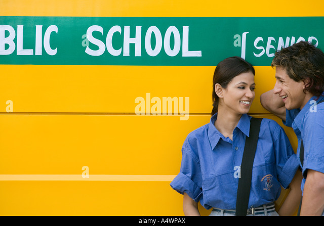 Student couple laughing in front of school bus - Stock-Bilder