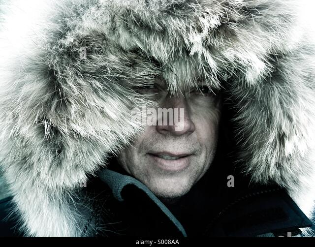 Arctic explorer braces himself against the weather extremes. - Stock Image