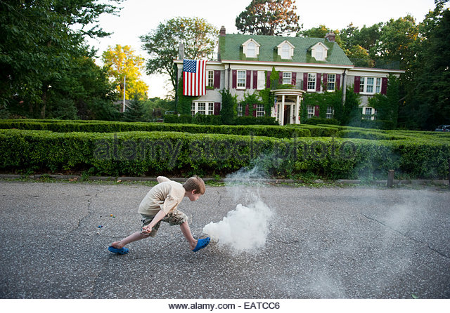 A young boy lights a smoke bomb in Lincoln, Nebraska. - Stock Image