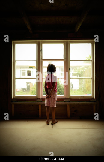 Girl by standing beside shed window - Stock Image