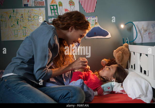 Mother telling her little daughter a bedtime story - Stock Image