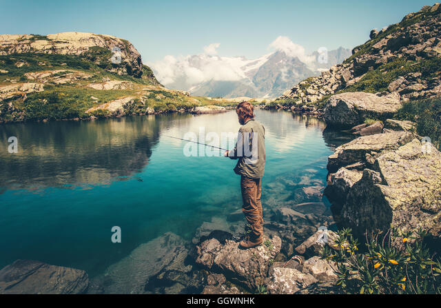 Young Man fishing on Lake with rod mountains landscape on background Travel Lifestyle concept summer vacations - Stock Image