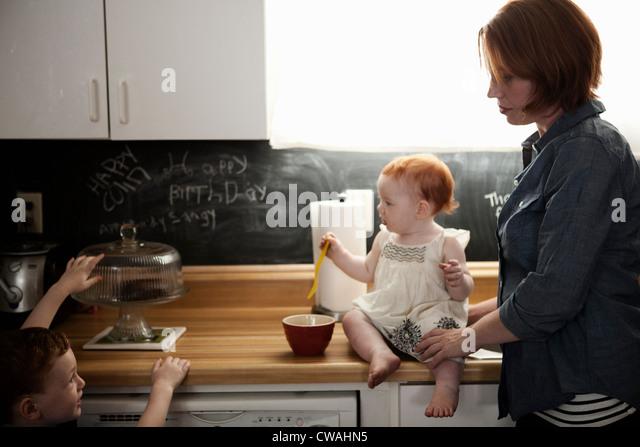 Mother in kitchen with two children - Stock-Bilder