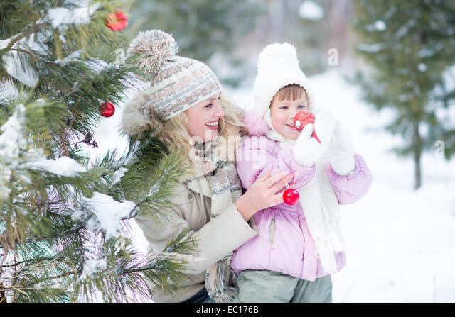 Happy parent and kid playing with christmas tree decorations outdoor - Stock Image