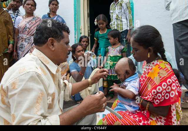Indian baby hair cutting ritual / puja in a rural indian village. Andhra Pradesh. India - Stock Image
