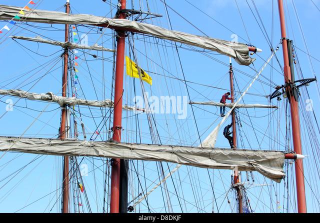 Two sailors climbing rig to reach yard of sailing ship - Stock Image