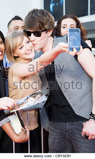 Fan taking picture of herself with celebrity - Stock Image
