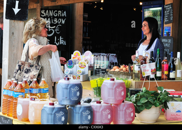 Woman buyer at a road side stall near Bezier South of France where they sell local grown fruit vegetables and wine - Stock Image