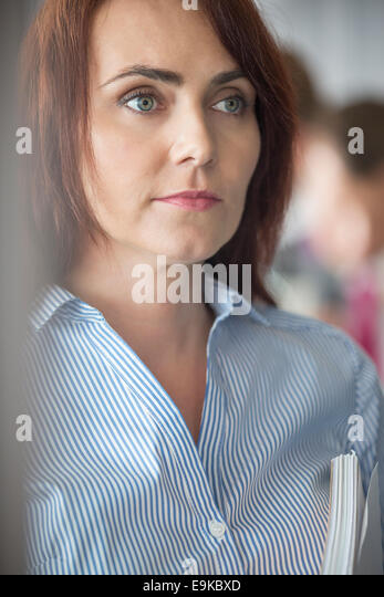 Mid-adult businesswoman looking away in office - Stock Image