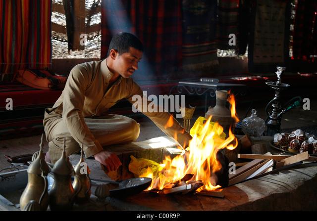 Man setting fire to make tea at a bedouin tent next to Qasr Kharana, Jordan. - Stock-Bilder