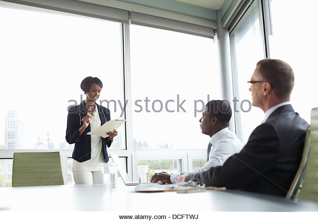 Female professional presenting to colleagues - Stock Image