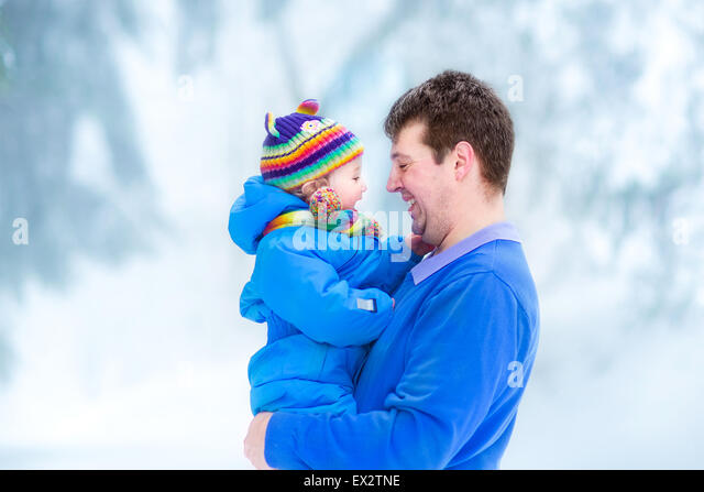 Young father playing with his funny baby in a snowy park - Stock Image