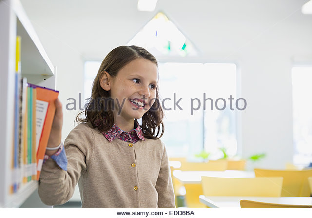 Smiling elementary student selecting book in library - Stock Image