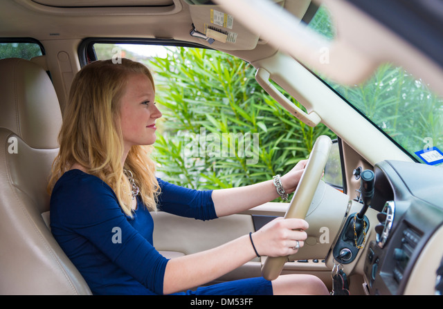 16 years old girl sitting in a large SUV car and is about to drive. She has received her drivers license just weeks - Stock Image