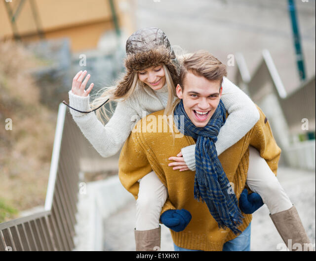 Portrait of cheerful man piggybacking woman on stairway - Stock Image