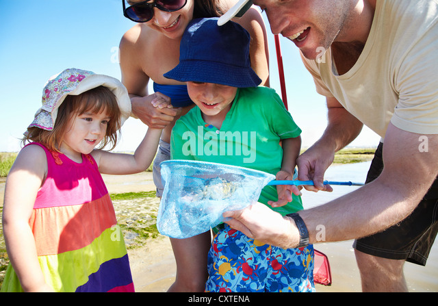 Family fishing with nets outdoors - Stock Image