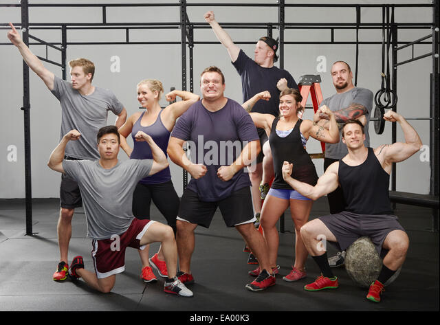 Portrait of eight people flexing muscles in gym - Stock Image