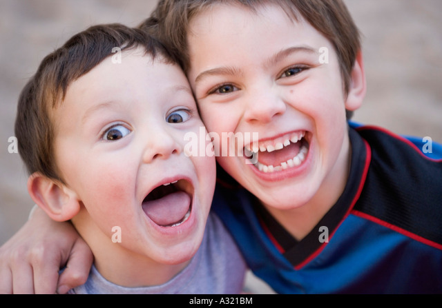 Brothers standing together and laughing - Stock-Bilder