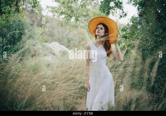 Caucasian woman wearing hat walking in tall grass - Stock Image