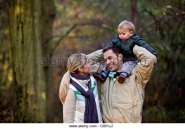 A family standing in the park, father carrying his son on his shoulders - Stock Image