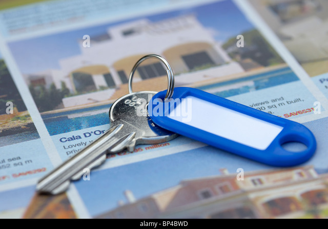 house keys lying on the foreign property section of a newspaper in the uk - Stock Image