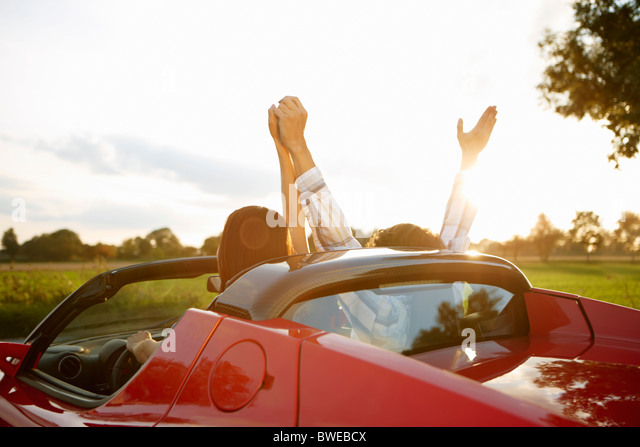 Couple in an electric sports car, fun - Stock Image