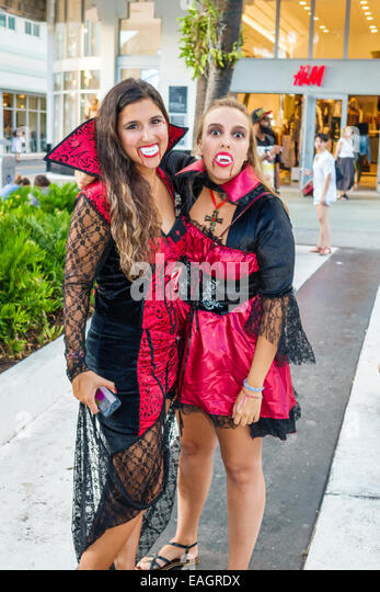 Miami Beach Florida Lincoln Road pedestrian mall Halloween costume woman wearing vampire friends outfit character - Stock Image