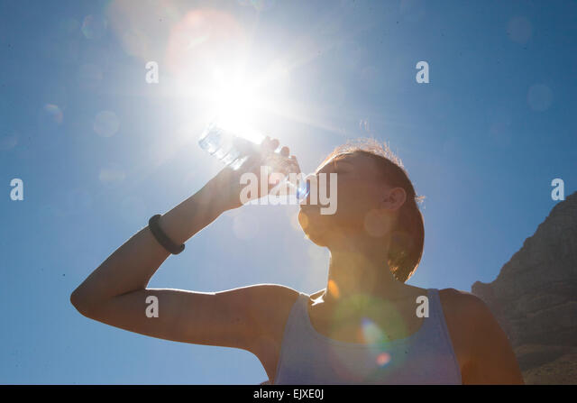 Woman Drinking Water from Bottle against Blue Sky - Stock Image