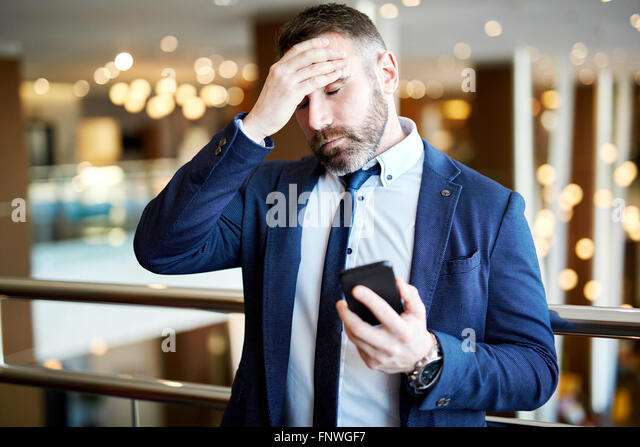 Fatigue man with cellphone touching his forehead - Stock Image