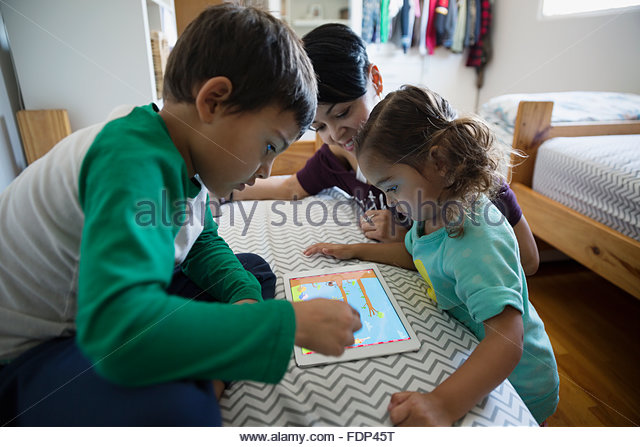 Mother and children playing game on digital tablet - Stock Image
