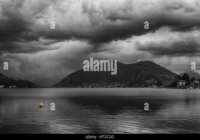cloudy afternoon over the Lugano Lake with yellow floating buoy, Porto Ceresio - Varese - Italy - Stock Image