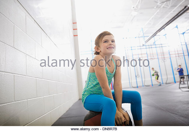 Girl sitting on medicine ball - Stock Image
