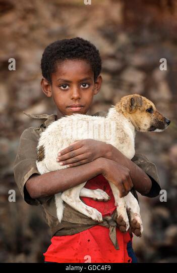 Ethiopian boy holding timid pet dog. The road to Debark, Ethiopia. - Stock Image