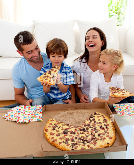 Parents and children eating pizza in living-room - Stock Image