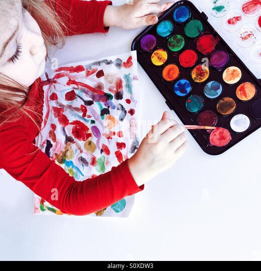 Image of a young girl using water colors to make designs on paper. - Stock Image