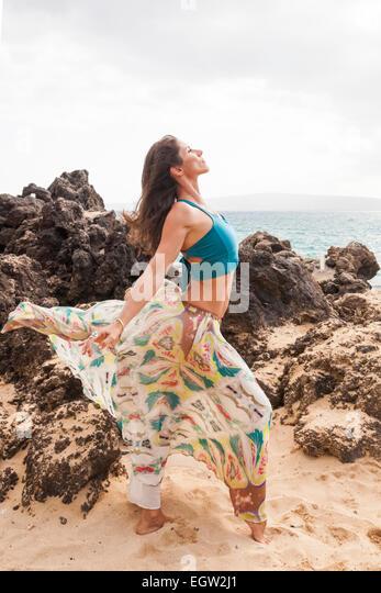 Woman on beach with a flowing skirt. - Stock-Bilder