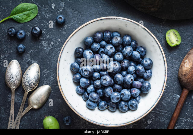 Still life of fresh blueberries in bowl, vintage cutlery, baby kiwi and spinach on stone table. Top view, closeup - Stock Image