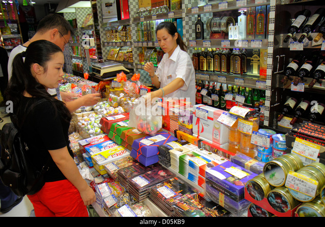 Shanghai China Huangpu District East Nanjing Road business store candy sweets treats Asian woman clerk job employee - Stock Image