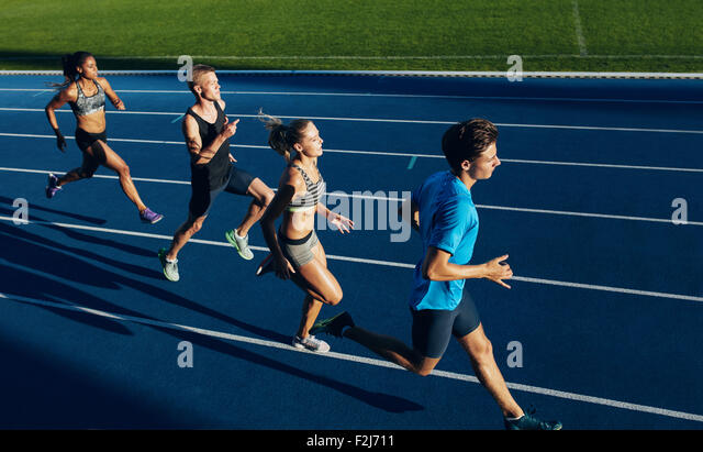 Group of multiracial athletes practicing running on racetrack. Male and female athletes during running session at - Stock Image