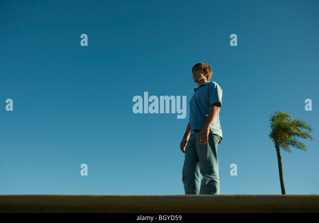 Young man standing on ledge, low angle view - Stock Image