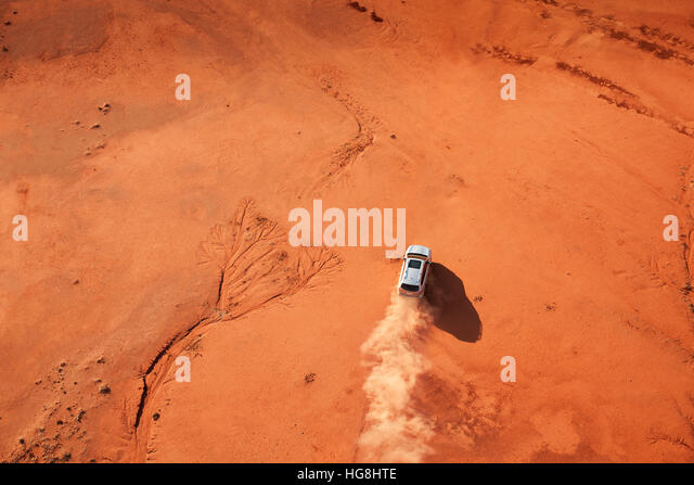 Bird's eye view looking over a car driving through the Australian outback red desert - Stock-Bilder