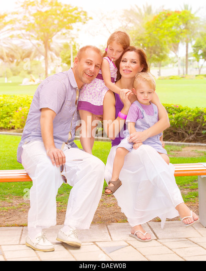 Cute family sitting on bench in the park, active lifestyle, little brother and sister with parent outdoors, parenthood - Stock Image