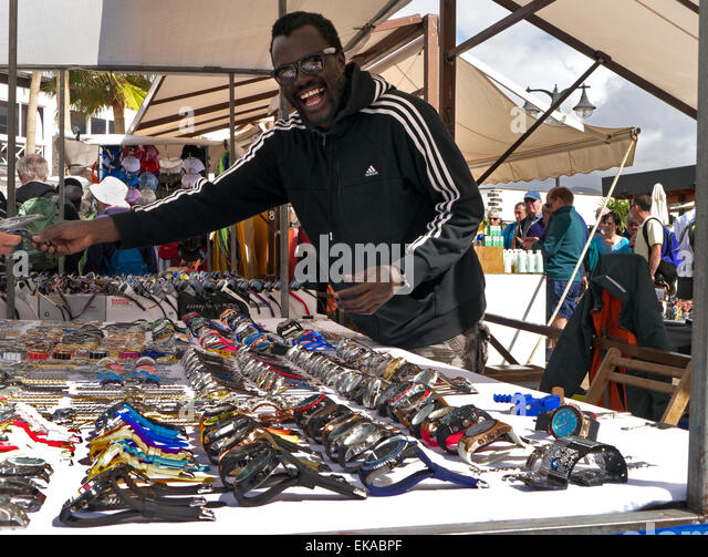Happy North African gentleman selling inexpensive counterfeit watches to tourists branded with luxury names like - Stock Image
