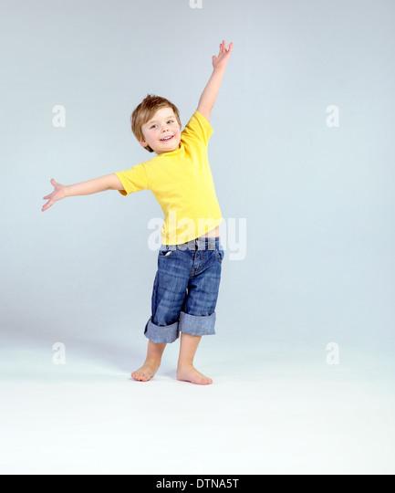 Joyful little man playing a plane - Stock Image