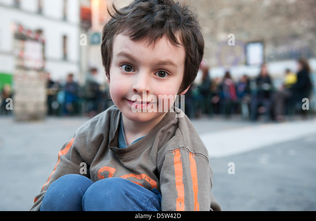 Boy sitting outdoors in urban setting, portrait - Stock Image