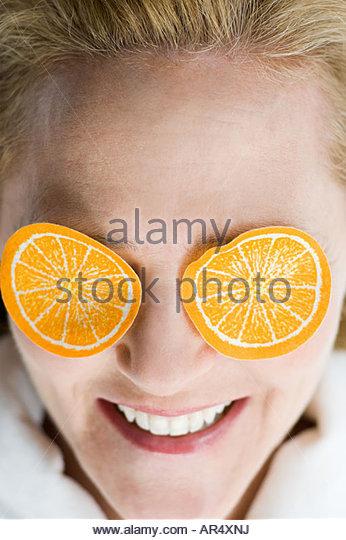 Woman with fake orange slices on eyes - Stock Image