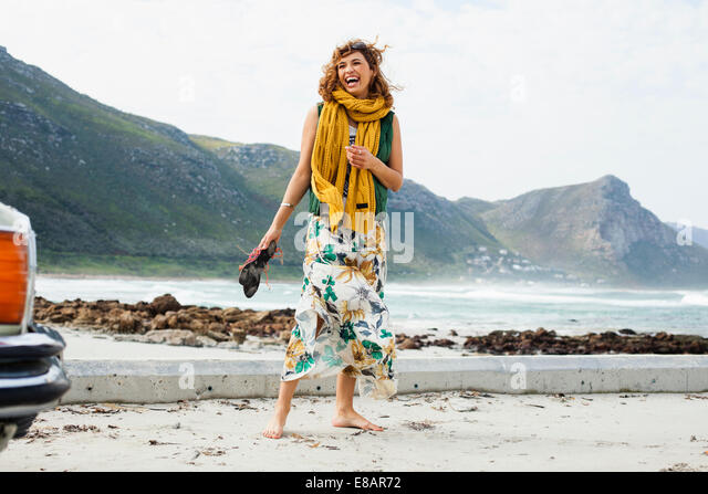 Young woman laughing on beach, Cape Town, Western Cape, South Africa - Stock Image