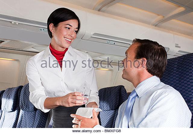 Air stewardess giving drink to passenger - Stock-Bilder
